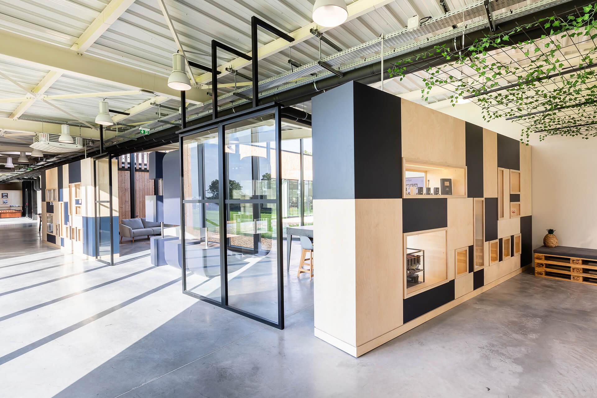 espaço de receção e lounge de centro de negócios com estante e acabamentos em madeira