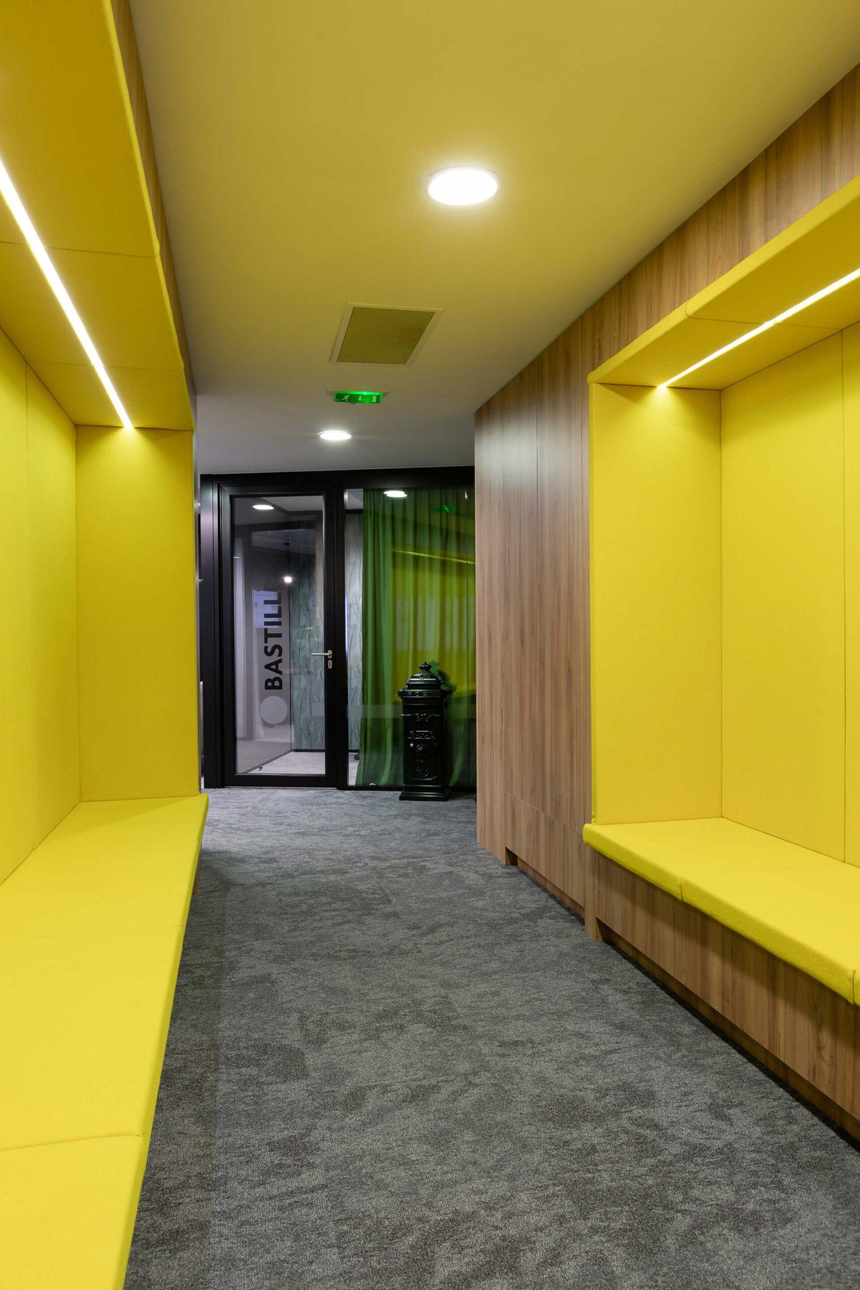 corredor com bancos embutidos amarelos e em madeira