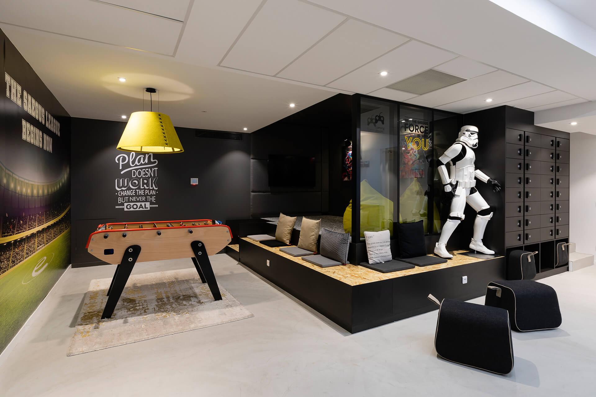 espaço de lazer com stormtrooper, mesa de matrecos, espaço de arrumação e bancos em madeira