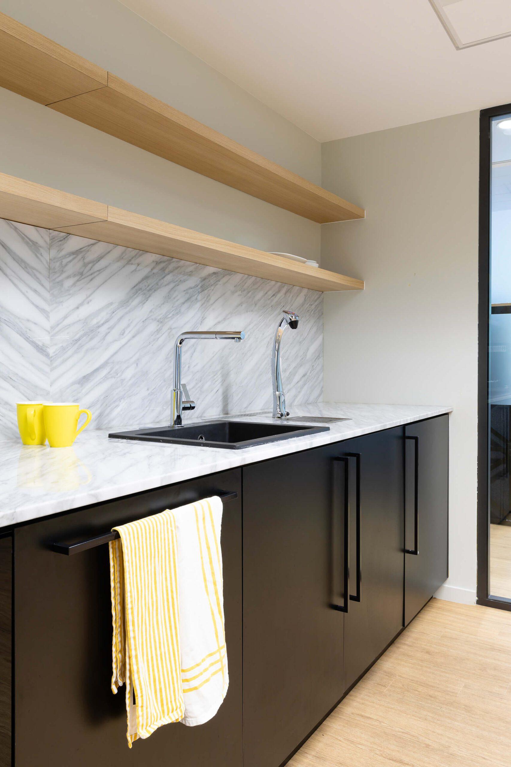 bancada de cozinha em madeira preta e castanha com decoração