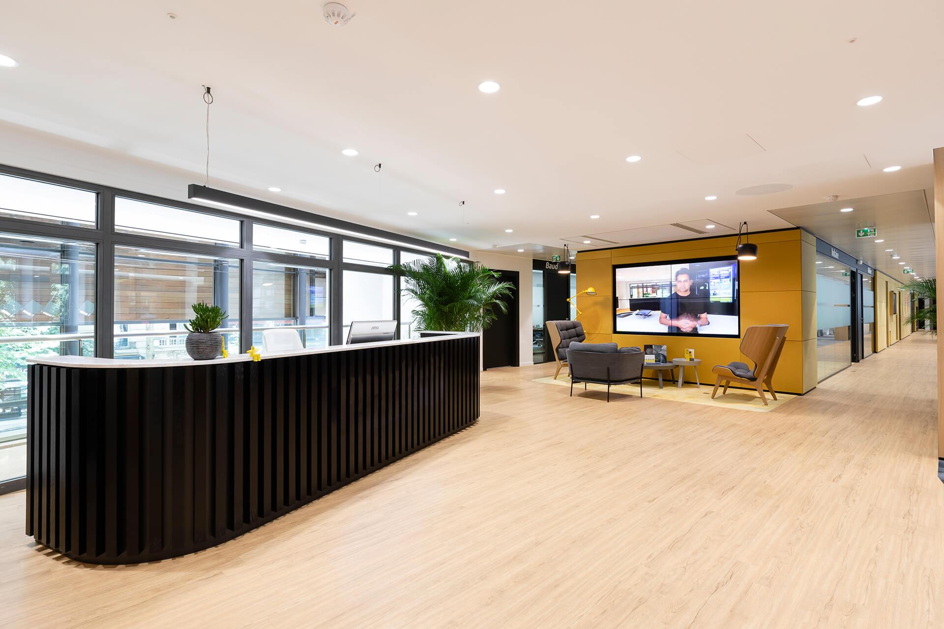 balcão em madeira ripada e espaço lounge com cadeiras e tela