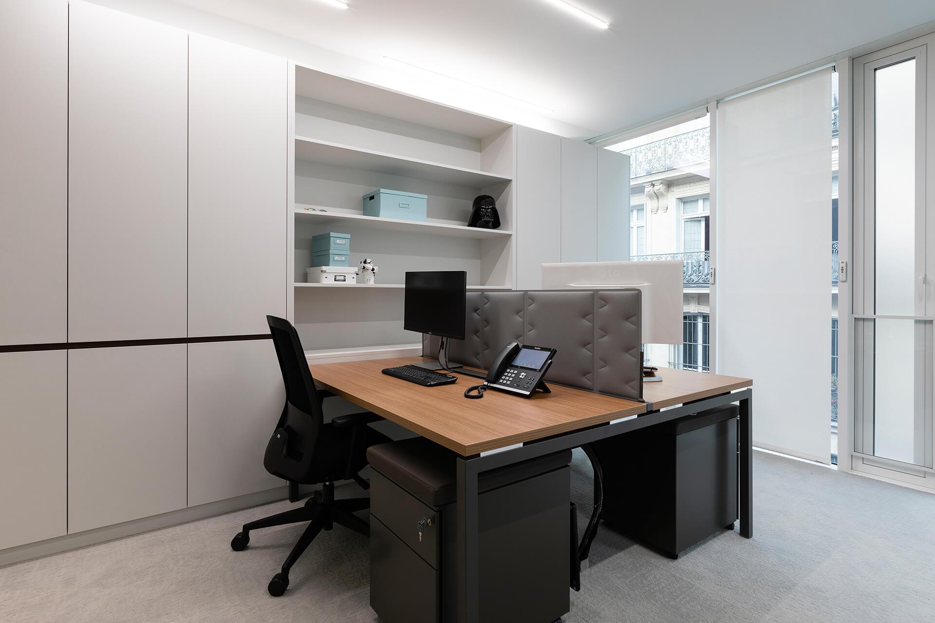escritório com estantes brancas e mesa em madeira