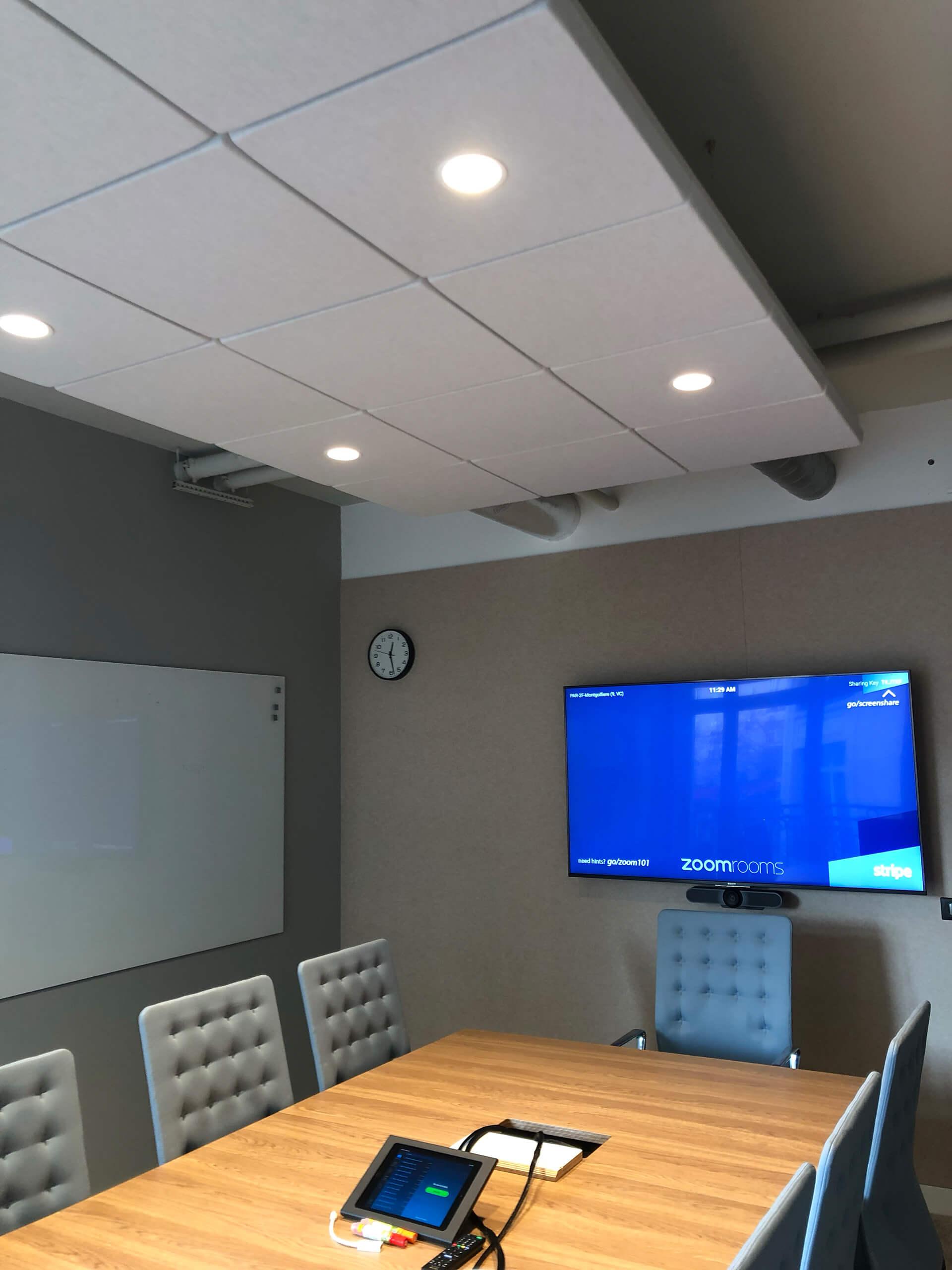 sala de reuniões com mesa em madeira, cadeiras em pele, tela e quadro