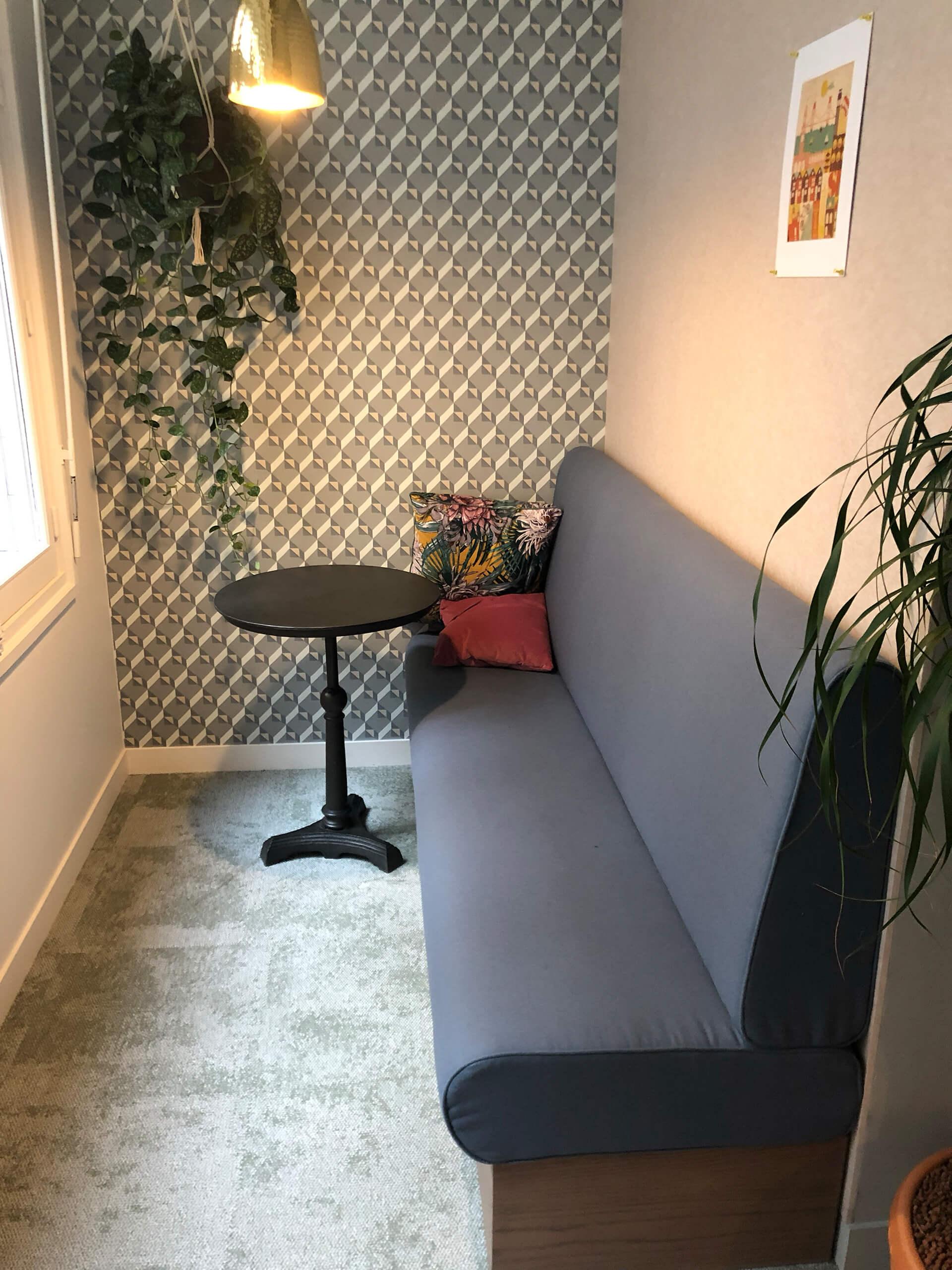 espaço lounge com sofá, mesa em madeira preta e decoração com papel de parede retro
