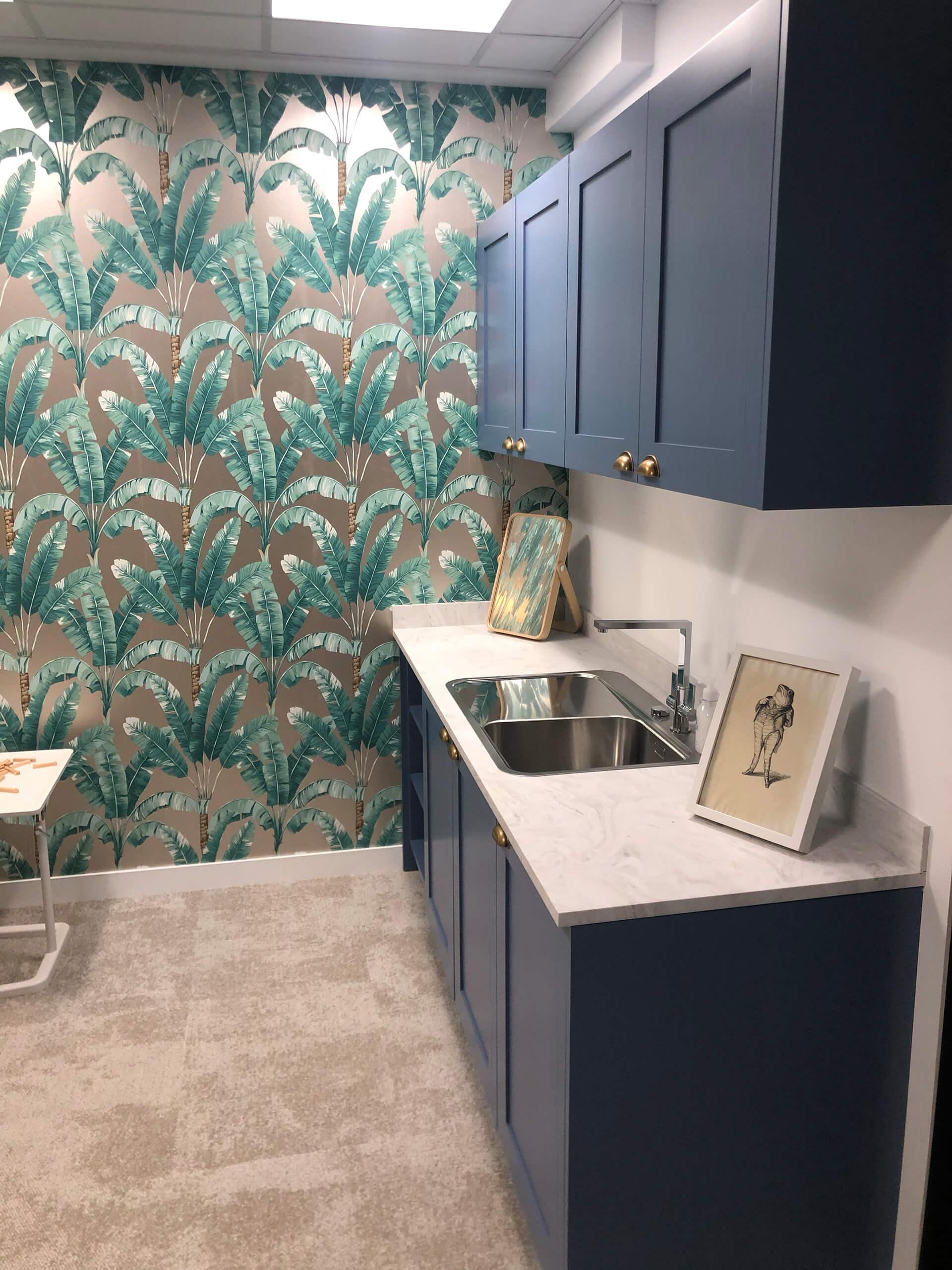 Cozinha preta com detalhes dourados, papel de parede palmeiras.