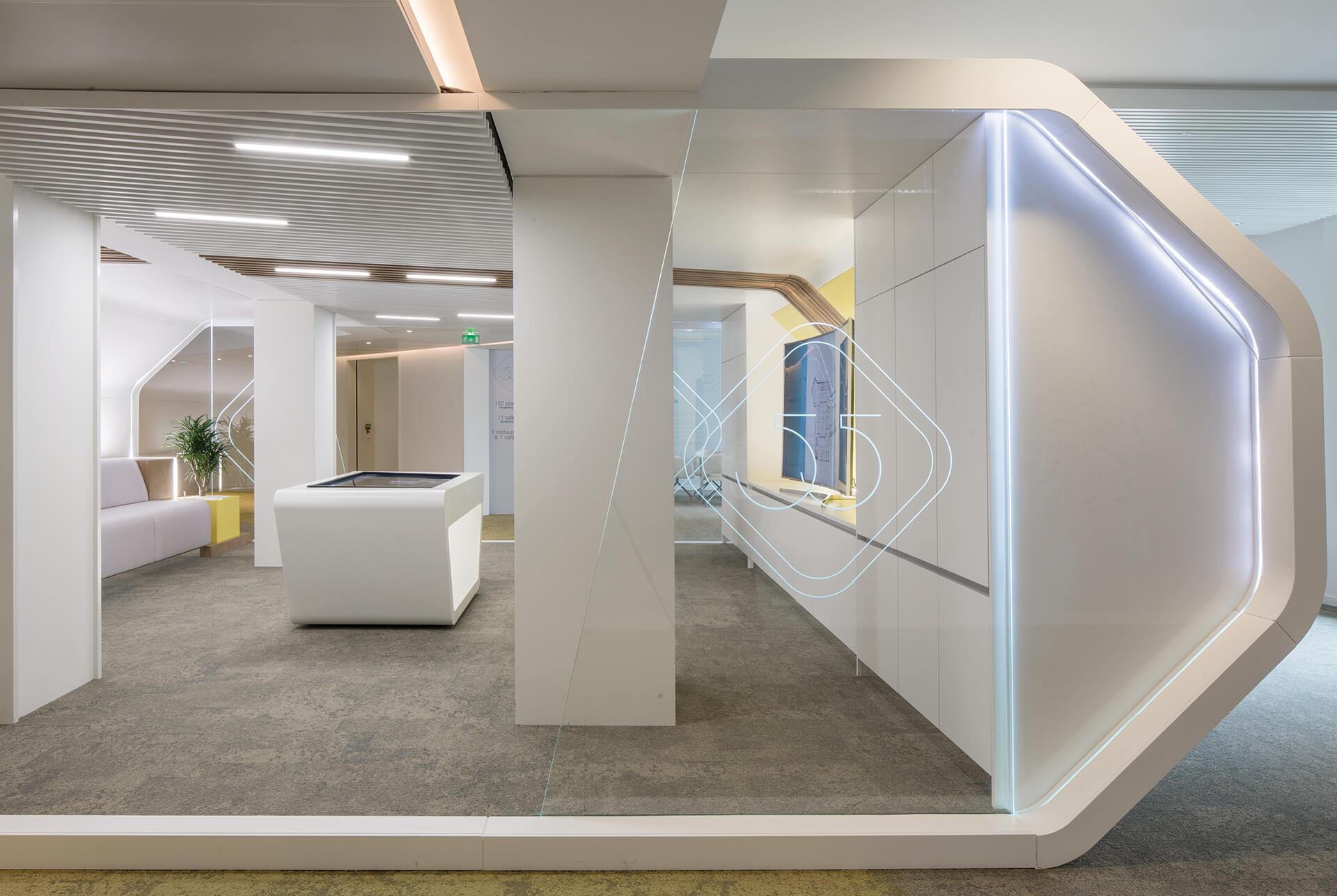 espaço imobiliário com parede em vidro retroiluminada e acabamentos de luxo