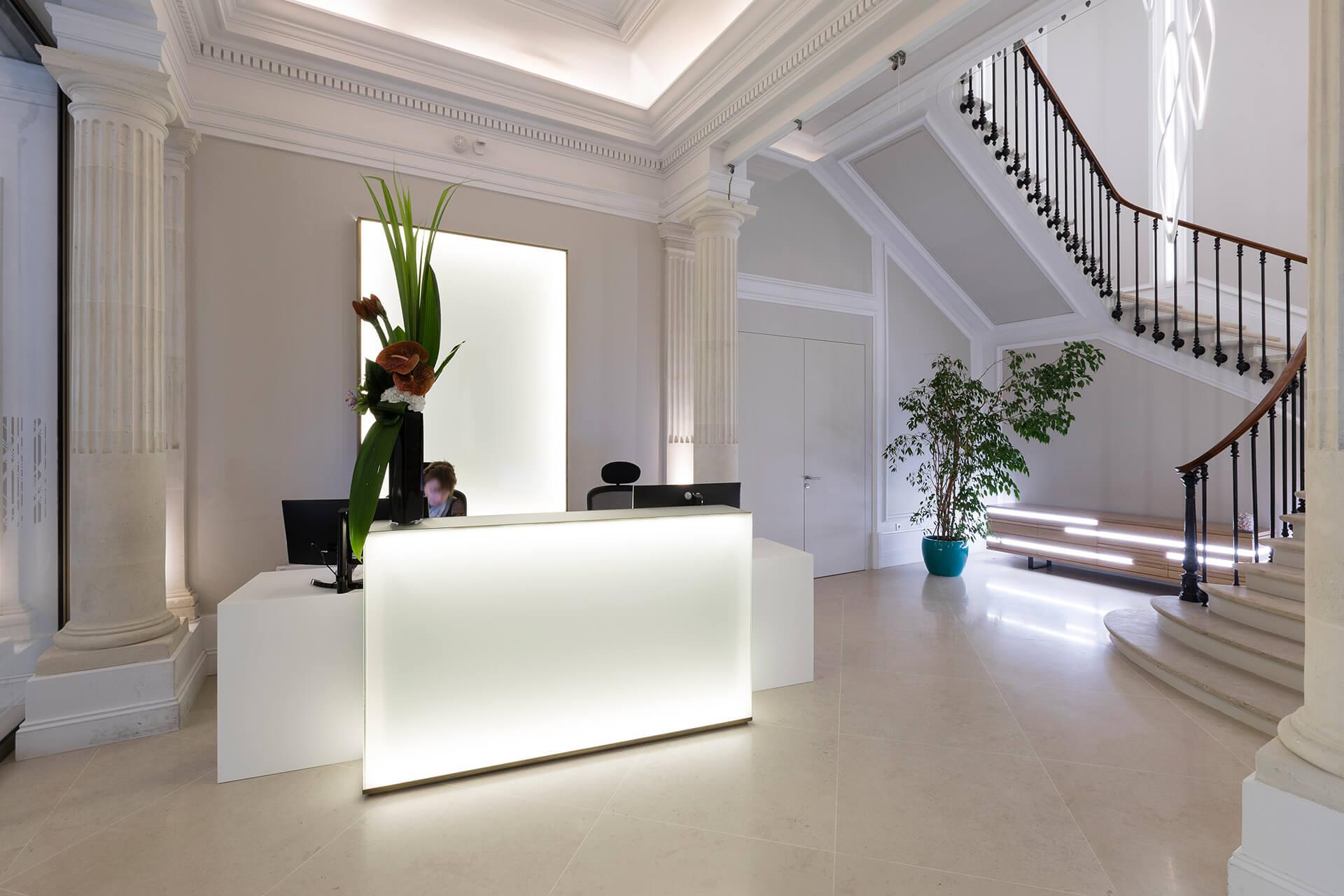 escadaria e receção com vaso e móvel de madeira retroiluminado