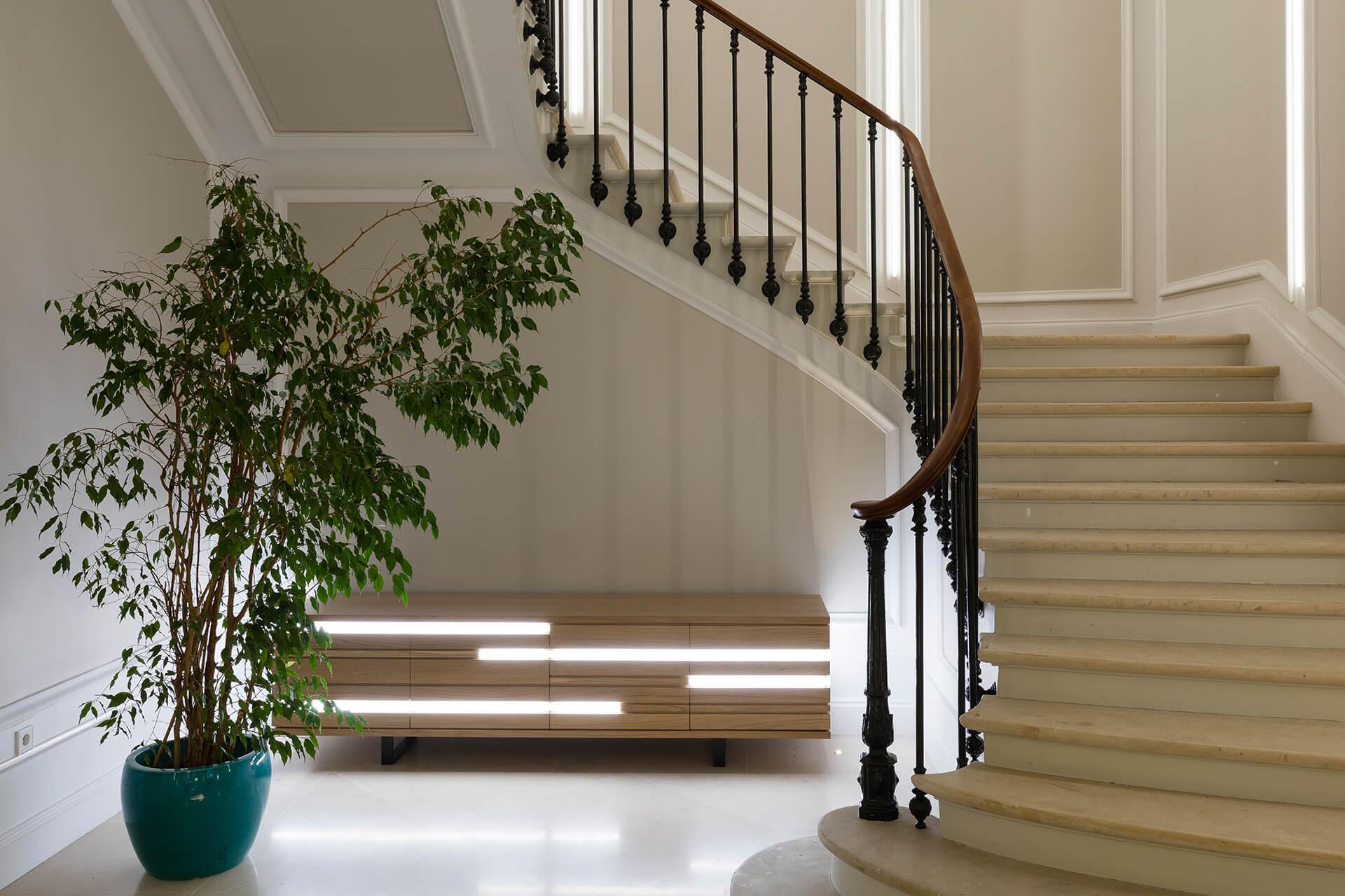 escadaria com vaso e móvel de madeira retroiluminado