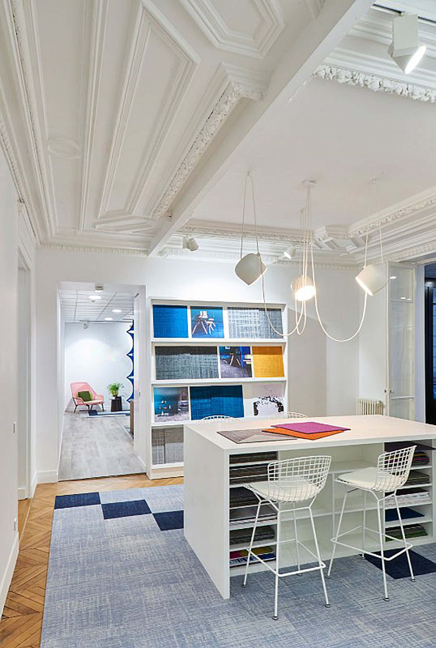 Espaço textil com tecidos em móvel branco e mesa com cadeiras altas.