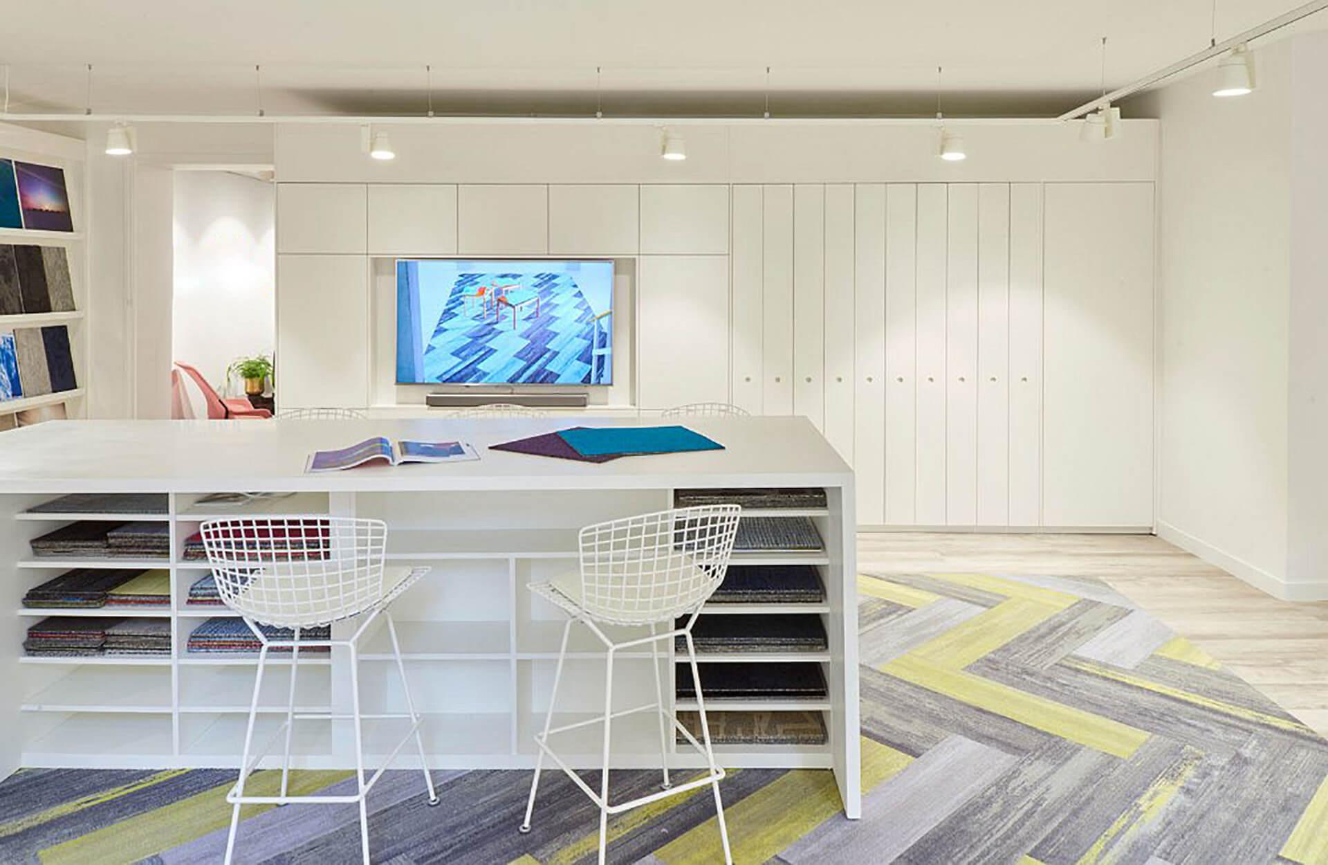 Espaço textil produzido pela Eben com tecidos em móvel branco e mesa com cadeiras altas.